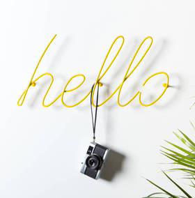 Hello! Greeting card. The writing on the wall. Yellow color. White background. White wall. A camera on the white wall. Free Download 2021 greeting card
